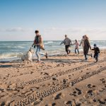 family-playing-on-the-beach-with-their-leashed-dog